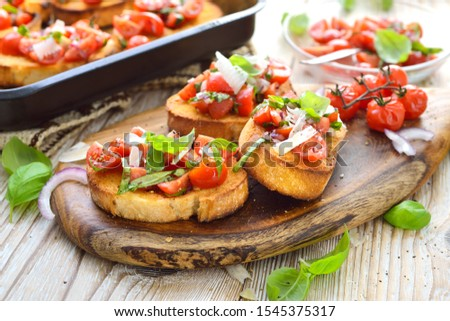 Warm Italian bruschetta: Crispy baked Italian ciabatta bread with cherry tomatoes, basil and parmesan cheese, served as an appetizer Stock fotó ©