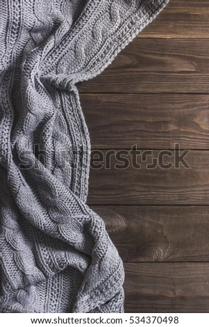 Warm Knitted crumpled gray blanket on a wooden background. Top view, space for text #534370498