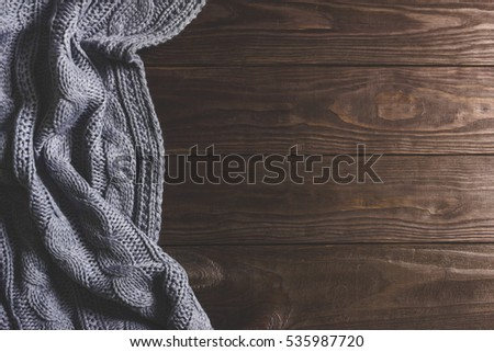 Warm Knitted crumpled gray blanket on a wooden background. Top view, space for text #535987720