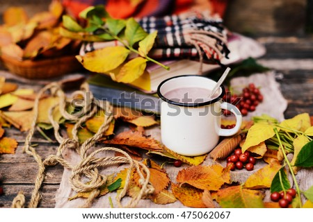 Warm knitted scarf and a book on a wooden tray. Peaceful Fall Fruit, Leaf, Acorn Still Life on Rustic . autumn still life with a cup of tea. Cup of tea with autumn leaves reflection on book  #475062067