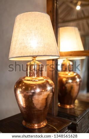 Warm lighting bronze modern lamp on wood table near mirror. #1348561628