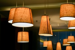 Warm lighting coming out from beautiful lamps on ceiling , while taking a hot cup of coffee in a trendy cafe with nice environment, Selective focus on central lamp