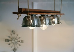 Warm lighting coming out from lamps inside beautiful utensils kitchen equipment, ropes and wood, hanged  from the ceiling Wall clock with forks and spoons on the background.