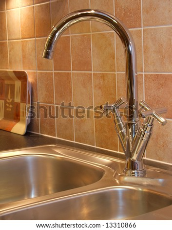Warm Modern contemporary kitchen taps and sink with tiles