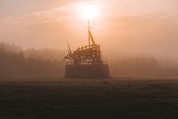 Warm morning landscape with thick orange fog, rising sun and wooden sculpture of a bull in a field, land-park of Nikola-Lenivets village
