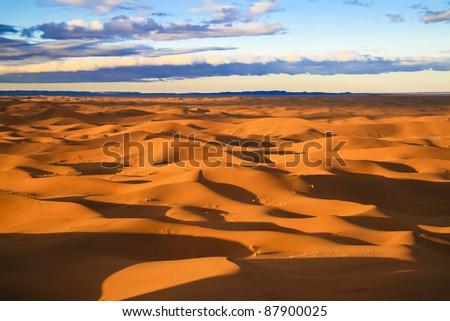 Warm morning light over never ending sand dunes in Morocco. - stock photo