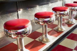 Warm morning sunlight highlights the simple but beautiful design of this classic diner counter with it's galvanized steel counter, bright chrome seats with red padding and bright red tiles.
