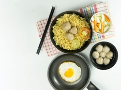 Warm noodles served with eggs and fresh tomatoes with meatballs on a black bowl and pickled on a white bowl and eggs on a white background