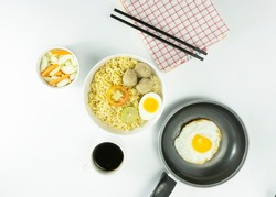 Warm noodles served with fresh tomatoes and meatballs on a white round bowl and pickles on a white bowl on a white background