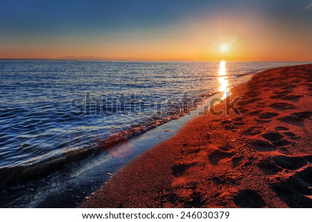 Warm ocean beach sunrise with breaking wave and footprints in sand