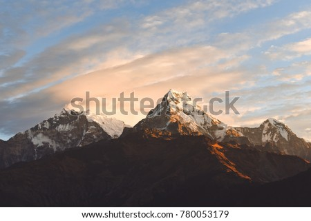 Warm pink and orange sunrise light over Annapurna mountain range with beautiful clouds, view from Poon hill in Himalayas, Nepal #780053179