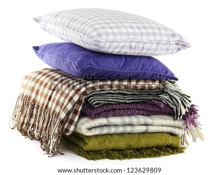 Warm plaids and colorful pillows isolated on white