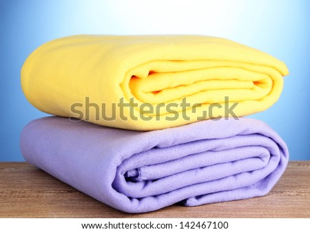Warm plaids on wooden table, on blue background