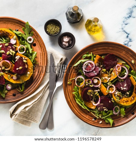 warm salad of baked pumpkin and beets with arugula and seeds on a marble table. healthy vegan cuisine for the whole family