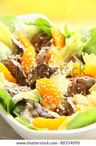 Warm salad with chicken liver, lettuce, tangerine and sesame seeds