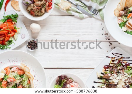 Warm salads frame on white wood flat lay. Top view on restaurant table with assortment of meat side dishes, free space. Buffet, banquet, menu concept