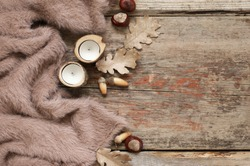 Warm soft blanket, candles, dry oak leaves with acorns and chestnuts on old rustic wood background. Autumnal cozy still life. Top view point.