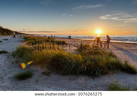 Warm summer sunset. Beach landscape with silhouettes of people on the background. Jurmala resort, Latvia, Baltic Sea. Vacation concept