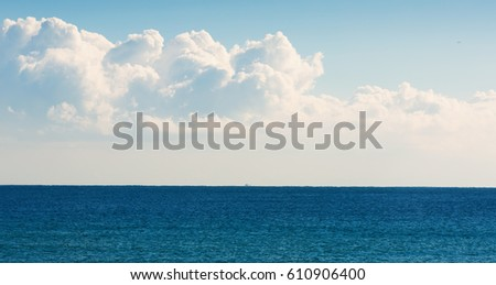 Warm sunny day with light clouds at deep blue sea #610906400