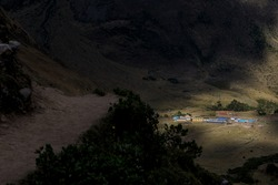 Warm, sunny light falling over the Salkantaypampa camp seen from the trail leading to Humantay lake on the Salktantay trek in Peru. Adventure trekking in Peru on the famous Salkantay trek