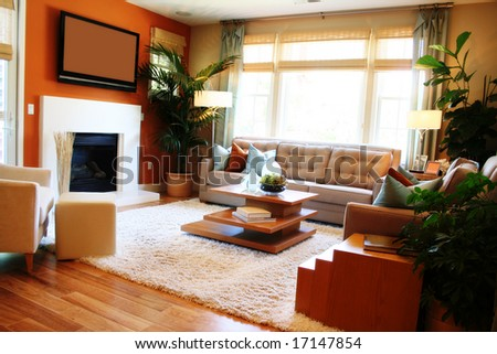 Warm, sunny living room with fireplace, TV and large window - stock photo