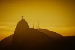 Warm Sunset with Christ Redeemer silhouette in Rio de Janeiro, Brazil