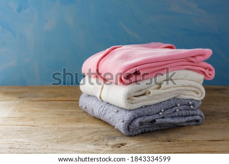 Warm sweaters piled on an old wooden table. Autumn and winter clothes With a faint light shining on Stock fotó ©