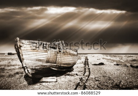 warm toned dreamy image of an abandoned wooden fishing boat on a shingle beach with a dramatic sunbeam sky in the background.
