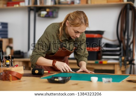 Warm toned portrait of female artisan making leather bags and shoes in workshop, copy space