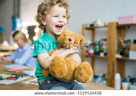 Warm toned portrait of happy curly haired kid laughing cheerfully and hugging teddy bear toy, copy space
