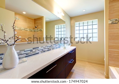 Warm tones bathroom. Chocolate wood cabinets with white counter tops, white vase with dry flowers amazing design interior