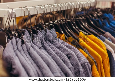 Warm top men's wear, shirts and sweaters, hang on a hanger. Sale of clothes in shop #1269001606