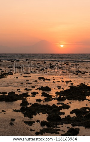 Warm tropical sunset over Agung volcano, the highest mountaint on Bali island, Indonesia with sea and stones on front