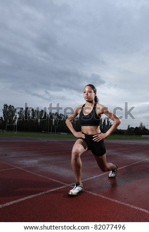 Warm up lunge exercise for quadriceps by fit young female athlete on athletics running track, wearing black lycra sports outfit and running spikes. Grey cloudy sky in background.