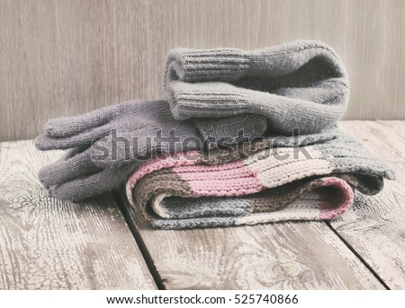 Warm winter knitted clothes - hat, scarf, gloves on a wooden background, female, selective focus, vintage toning
