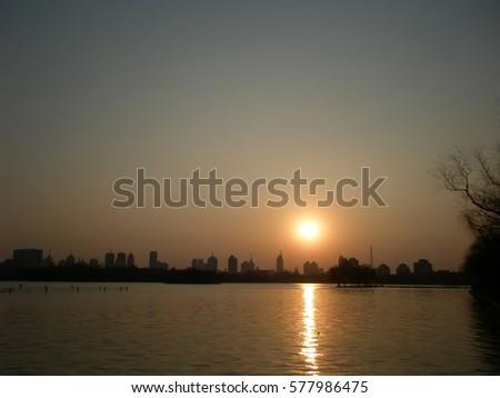 Warm winter sunset over lake at Jinan, Shandong province, China #577986475