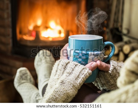 Warming and relaxing near fireplace with a cup of hot drink. #532151161