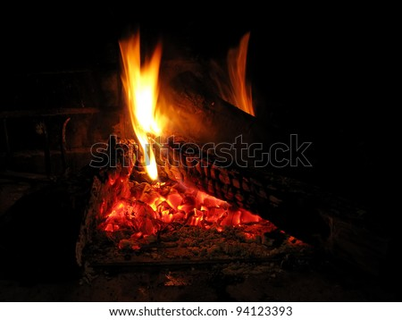 Warming fireplace in winter, at home. Close up of flames and firewood - stock photo