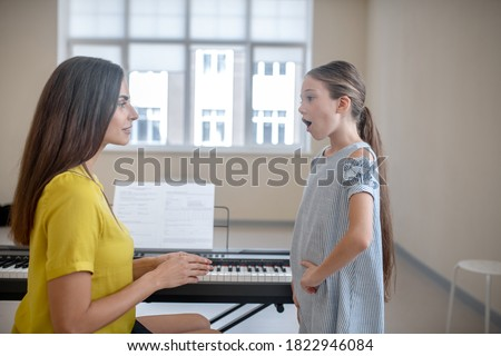 Warming up. Girl in a blue dress having a vocal lesson Photo stock ©