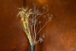 Warmth image with a dry flowers bouquet over an orange wall