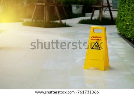 Warning Caution wet floor sign on wet tiles floor at outdoor walkway.