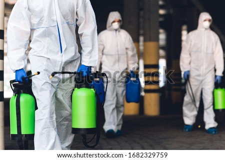 Warning, coronavirus disinfection. Men in virus protective suits carrying spray bottles with chemicals, blurred background Stockfoto ©