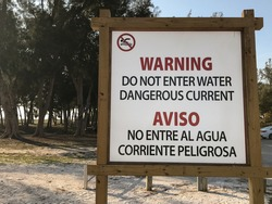 Warning Do Not Enter Water Dangerous Current Sign in English and Spanish. Aviso No Entre Al Agua Corriente Peligrosa
