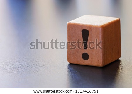 Warning exclamation mark on a wooden block to attract attention over a grey background with beams of light and copy space