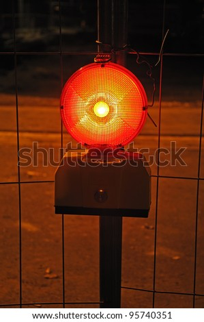 Warning light  Photo of a burning warning light in front of metal grid fence