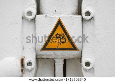 Warning sign about hands trapped between gears of a sluise gate Foto stock ©