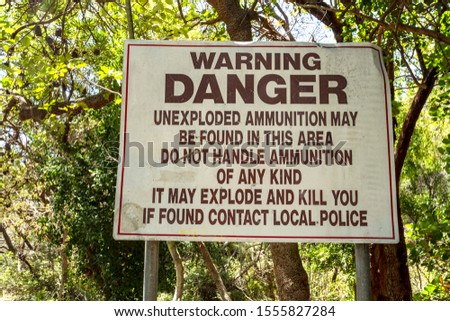 Warning sign announcing the danger of unexploded ammunition in the area, in Currimundi Beach, Queensland, Australia Stock photo ©
