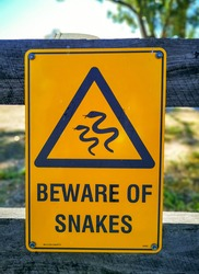 Warning sign beware of snakes in infested area.