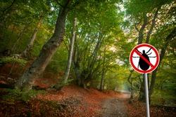 Warning sign beware  of ticks in nature forest. Transmitter Lyme disease and tick-borne meningitis (meningoencephalitis).