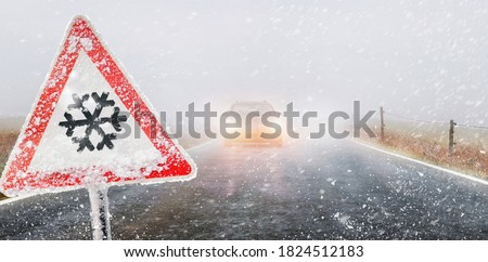 warning sign - first snow, road in the fog by car in the evening